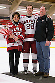 Chris Huxley (Harvard - 28) poses with his parents. - The Harvard University Crimson defeated the St. Lawrence University Saints 4-3 on senior night Saturday, February 26, 2011, at Bright Hockey Center in Cambridge, Massachusetts.