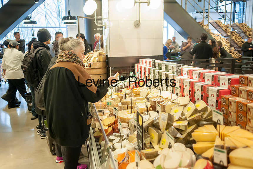 Shoppers chooses pre-cut packages of cheese in the new Whole Foods Market opposite Bryant Park in New York on opening day Saturday, January 28, 2017. The store in Midtown Manhattan is the chain's 11th store to open in the city. The store has a large selection of prepared foods from a diverse group of vendors inside the store.  (© Richard B. Levine)