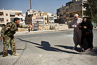 A rebel Free Syrian Army (FSA) fighter (left) encourages an elderly couple to hurry across a street where they are exposed to Syrian Army sniper fire near the front lines of Salaheddin in Aleppo.