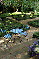 A garden table and two chairs placed on a gravel path inject a note of bright turqouise into the garden