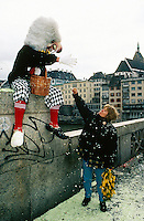 Switzerland. Basel. Fasnacht Carnival. On a bridge. A disguised person with white hair, a big nose, red socks, white gloves and pants with checked material throws confetti on a woman smoking a cigarette and holding yellow mimosa flowers. © 1997 Didier Ruef
