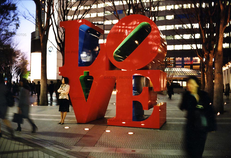 A Japanse woman waits for someone under the LOVE sculpture by pop art arstist, Robert Indiana, in Tokyo, Japan.