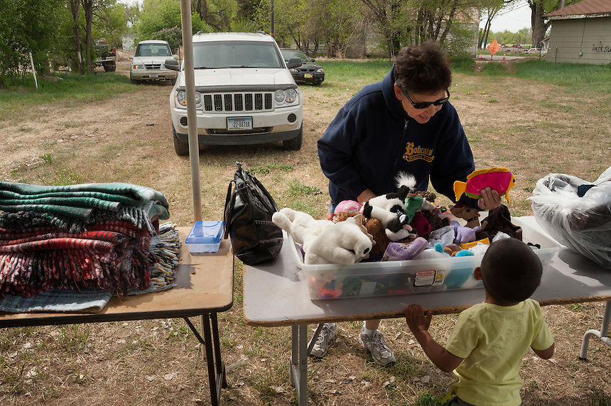 Lynda White Man Runs Him shows a toy to a young customer at a yard sale held to raise money to send a young granddaughter to a camp for newly diagnosed diabetics, Thursday, May 16, 2013. Poverty is endemic on the reservation. Pending new ports for shipment to Asia through either the U.S. or Canada, Cloud Peak Energey hopes to open new high-grade coal mines on and near the Crow Reservation in southern Montana. The tribe is equally hopeful the new mines would bring long-awaited economic stability to the tribe. (Kevin Moloney for the New York Times)