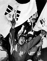 This anti-Communist North Korean just released from a prisoner of war camp is serving as a kind of cheerleader for fellow ex-POW's as they shout their joy of reaching Seoul.  The flags are of the Republic of South Korea.  Ca. 1953-54.  Gravy. (USIA)<br /> Exact Date Shot Unknown<br /> NARA FILE #:  306-PS-54-1497<br /> WAR &amp; CONFLICT BOOK #:  1497