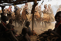 This party takes place under a tent made from leaves and rubber sheets donated by NGO's for agriculture that are now being used to create a beer hall...They are partying because there are 14 Bull Jumpers in the Karo tribe that will go through the manhood ceremony and this only happens once in a generation.  Even though the food aid is being abused, the rest of the traditions here are symbolic of an intact culture that behaves this way for themselves, not because of tourists...Food aid is problematic because most of the grain that is handed out is subsequently fermented for alcohol...