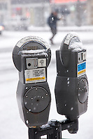 Coin operated parking meters in a snowstorm in White Plains, New York, USA