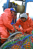 Deckhand Tiffane Scarlatos (left) and Daniel Hees sew a damaged net on the F/V Progress, a dragger, also known as a trawler, fishes for pollock in the Bering Sea.