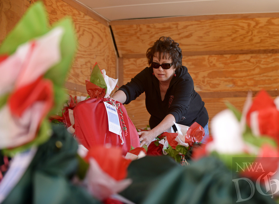 NWA Democrat-Gazette/BEN GOFF @NWABENGOFF<br /> Tonya Martin of Springdale loads food bags into a trailer on Sunday Dec. 6, 2015 as volunteers with the Chase Family Foundation distribute food for home-bound seniors and their pets. The organization's annual holiday distribution seeks to provide enough food for seniors and their pets to get through the holidays and periods of inclement whether when Meals on Wheels doesn't operate.