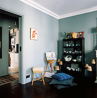 In one corner of the informal blue dining room, stools and cushions are carefully arranged, whilst ceramic and glass objects are displayed in a cabinet