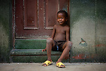 portrait of young cuban boy sitting on stair stoop shirtless.