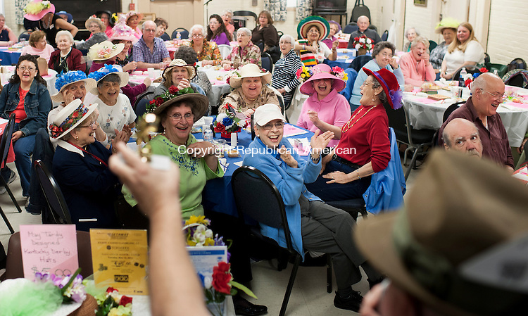 NAUGATUCK, CT-1 May 2015-050115EC08-  Members of the Naugatuck Senior Center cheer as an administrator holds up a trophy of a horse's bottom as a prize during Kentucky Derby Day. This is the tenth year the senior center marked the Kentucky Derby with it's own friendly competition. Members volunteered to be jockeys and were assigned a horse number. A roll of the dice determined if they advanced to a winning position. The senior center was packed with fancy hats and a Kentucky-themed dinner. Members of the U.S. Army handed out roses. Erin Covey Republican-American