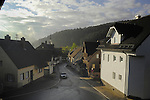 Early morning light, illuminating homes showing smoke rising from chimneys in the Black forest village of Tennenbron, Schramberg,  Wurttemburg, Germany.