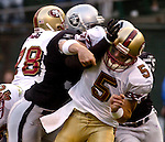 San Francisco 49ers quarterback Jeff Garcia (5) gets hit on Saturday, August 24, 2002, in Oakland, California. The Raiders defeated the 49ers 17-10 in a preseason game.