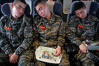 South Korean marines sleep on the ferry traveling to the mainland from the Yeonpyeong island that lays just inside the South Korean side of the Northern Limit Line (NLL) in Yellow Sea April 10, 2014. In 2010 North Korea fired multiple shells onto the island killing four people, including two civilians in a first such attack since the end of the 1950-53 Korean War. In subsequent years, the South Korean government has increased its military presence on the islands. Cliff tops are adorned with cruise missiles capable of striking Pyongyang, and the beaches are lined with barbed wire, soldiers, and mines. The two sides are still technically at war as the conflict ended in a mere truce, not a treaty. Picture taken April 10, 2014. REUTERS/Damir Sagolj (SOUTH KOREA)
