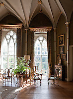 The great gothic music room, with its floor-to-ceiling tracery windows and gilded gothic pelmets