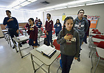 Yarely Arellano (front) recites the pledge of allegiance to the US flag at the beginning of class in the Lydia Paterson Institute in El Paso, Texas. Arrelano, 20, a U.S. citizen, travels across the border every day from her home in Juarez, Mexico, to study at the United Methodist-sponsored high school.