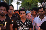 An Israeli woman says a prayer amongst Eritrean migrants in Tel Aviv, Israel, during a memorial ceremony for Haftom Zarhum, a 29 year-old Eritrean migrant who was shot by security men and then lynched by an Israeli mob. Three days earlier, after a Palestinian gunman fatally-attacked Israelis in the southern city of Be'er Sheva, Haftom Zarhum was mistakingly thought to be the Palestinian attacker by a security man.