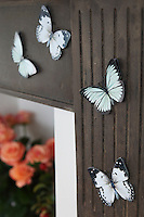 Detail of card butterflies attached to the iron fire surround in Kally Ellis's kitchen