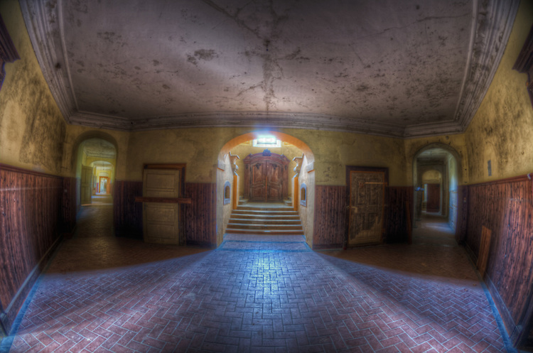 An abandoned palace in East Germany with brick floor in hallway
