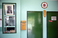 "Kenya. Rift Valley province. Kasambara (20 km from Nakuru). Rhein-Valley hospital is ran by a swiss non-governmental organization (NGO). Reception hall. A picture of the kenyan president Mwai Kibaki. Suggestion box. Blue walls and green doors. Consultation room with a sign saying "" Free"". A clock with a red apple.  © 2008 Didier Ruef"