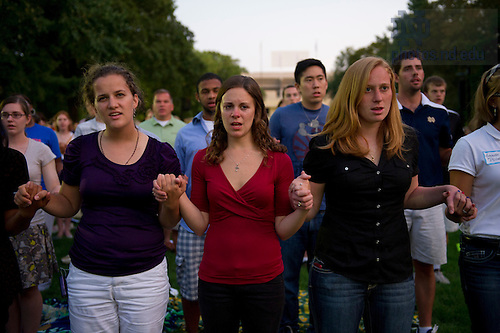 September 11, 2011; Notre Dame students and guests join hands and pray during a mass of remembrance for the 911 attack victims in the Hesburgh Library Quad at the University of Notre Dame. Photo by Barbara Johnston/University of Notre Dame