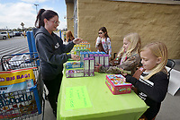 NWA Democrat-Gazette/BEN GOFF @NWABENGOFF<br /> Janell Taylor (from left) of Elm Springs buys Girl Scout Cookies from Emma Griggs, 9, Caroline Barnett and Olivia Tingley, 8, Saturday, March 12, 2017, while Girl Scout Brownie Troop 5343 holds a sale outside the Wal-Mart on Elm Springs Road in Springdale. The troop plans to donate $200 from the sale to the Springdale Animal Shelter and was also accepting donations to give cookies to the Springdale Police Department.