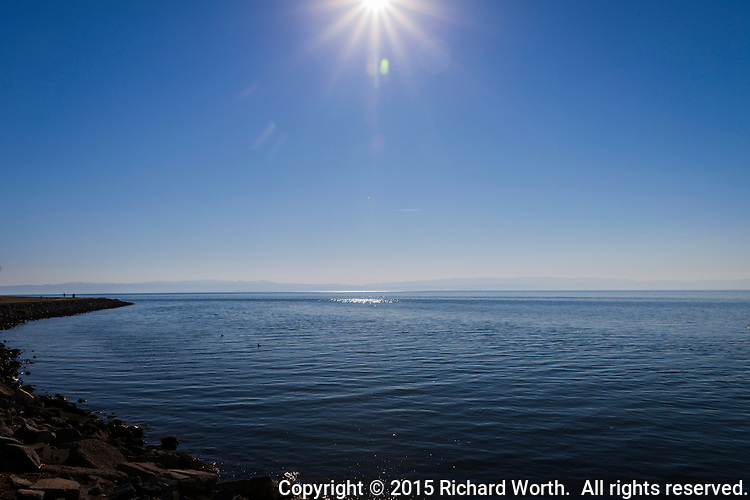 Blue water stretches to the horizon and meets the faint undulating lines of the Santa Cruz Mountains while a beaming sun shines  down from a clear blue sky.