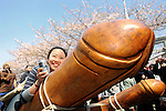 A woman straddles  wooden phallus during the Kanamara Festival, better known as the Penis Festival, in Kawasaki, Japan. Kanamara means metal phallus, so named after a story dating back hundreds of years in which a local blacksmith made an iron phallus to protect a girl who was thought to be curse. Today, the festival participants are largely prostitutes STDs.