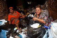 2011 Mokattam Garbage City (alla periferia del Cairo) il quartiere copto dove si vive in mezzo alla spazzatura raccolta: due donne dividono la spazzatura, sorridendo, suburbs of Cairo, the Coptic quarter where people live in the midst of garbage collection: two women dividing the garbage, smiling.