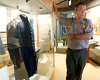 STAFF PHOTO JASON IVESTER --07/17/2014--<br /> Troy Banzhaf describes the Civil War frock worn by Lt. William B. Chapman on Thursday, July 17, 2014, inside the museum at the Pea Ridge National Military Park.