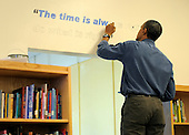 United States President Barack Obama paints a quote (&quot; The time is always right to do what is right &quot;) from Martin Luther King, Jr as he joins volunteers in a library as they participate in a service project, at Browne Education Center, in Washington, DC, USA, on the Martin Luther King Jr national holiday, 16 January 2012. The project was in memory of the legacy of community service, promoted by the late civil rights leader, who was assassinated in 1968..Credit: Mike Theiler / Pool via CNP