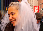 Manhattan, New York, USA: Smiling bride puts on coat after posing, wearing just wedding dress, for wedding photos in Times Square, NYC, on Tuesday, January 24, 2012, after their City Hall marriage ceremony. Temperatures were unseasonably warm, reaching 52°F / 11°C mid-afternoon.