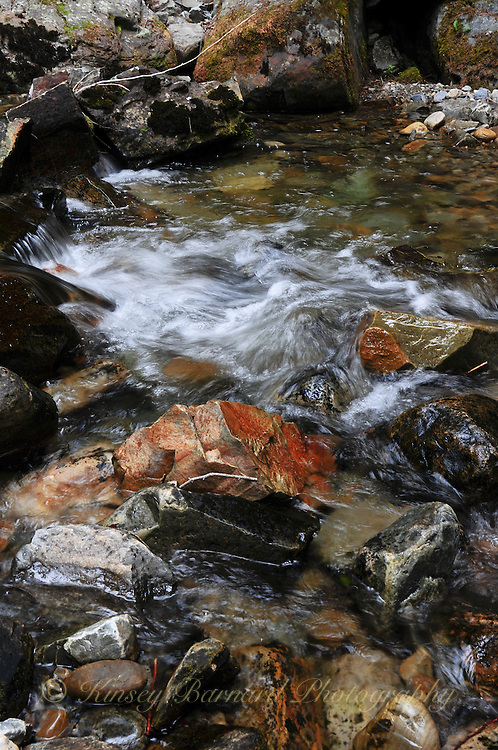 little northfork Creek in the Kootenai National Forest. Slightly stilled water flowing over colorful river rocks