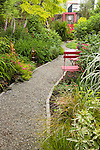 a gravel garden path leads between lush beds, past red painted metal chairs, and towards a red painted door  used as funky garden art at the far end in this residential bakyard garden that has removed its lawn in place of lush beds of flowers and foliage