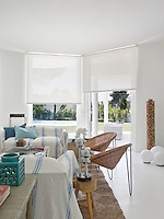 Large white roller blinds covering the living room windows offer protection from the intense Spanish sunlight and add to the serene feel of the all white living room