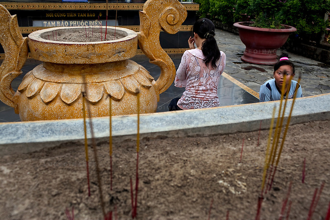 """A mother and daughter pray to a statue of """"Phat Thich Ca Mau Ni"""" or """"Sakyamuni Buddha"""" at the Giac Lam Pagoda in Tan Binh District in Ho Chi Minh City, Vietnam. Photo taken Tuesday, May 4, 2010....Kevin German / LUCEO"""