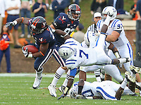 Virginia FB Rashawn Jackson (31) leaps over defenders as Duke cornerback Leon Wright (7) tries to make the tackle during an ACC football game Saturday in Charlottesville, VA. Duke won 28-17. Photo/Andrew Shurtleff