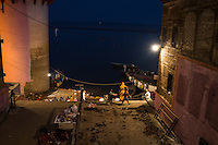 Boatmen's children selling flowers and candles are seen in the dark and narrow alleyways leading to the banks of the holy river Ganges where tourists come to witness the nightly Aarti prayers on the river banks in Varanasi, Uttar Pradesh, India as seen here on 18 November 2013. Guria runs a boat school targeting the boatmen's children, who are exposed and vulnerable to exploitation when they sell flowers and floating candles to the millions of tourists who come to Varanasi.