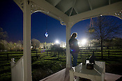Sara Shields on the front porch of her Hurdle Mills home as stadium lights for the Lattisville Grove Baptist Missionary church baseball field light up the night. A Zoning Enforcement Officer for Orange County was testing the output of the lights to ensure that it falls within zoning guidelines - it did not.