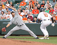 Casey Kotchman #13 of the Seattle Mariners misses base as Adam Jones #10 of the Baltimore Orioles steals first base during a MLB game at Camden Yards, on August 8 2010, in Baltimore, Maryland. Orioles won 5-4 in extra innings.