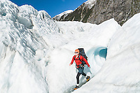 Female climber walking out of ice cave on Franz Josef Glacier, Westland National Park, West Coast, World Heritage Area, New Zealand