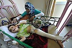Nurse Fozya Al-Bike comforts three-year old Aya Ali, in the Hekma Hospital in Misrata, Libya. The girl was seriously injured on June 12 when a wall, weakened by combat in her neighborhood between rebels and troops loyal to Libyan strongman Moammar Gadhafi, fell on top of her. She suffered a concussion, broken pelvis, broken leg, and other injuries. On her bed is a Koran. Fighting has raged in or near Misrata for months.