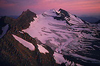 High mountains of Glacier National Park still have snow and ice although they are slowly melting.  Aerial at sunset shows ice in the summer on the north side of a mountain.
