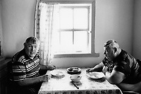 Kazakhstan. Dolon. Alexander Shakhvorostov (R) (fat man, born 1958) and his brother Anatoliy Shakhvorostov (G) ( born 1956) are in the house's kitchen and seat at table after lunch. Both men are mentally handicapped. They both suffer from mental deficiency and retardation. The village of Dolon is near the Semipalatinsk Polygon ( called today National Nuclear Center of Kazakhstan). Both men are second generation victim of the 456 atomic testing - 116 atmospheric, 340 underground - from 1949 to 1989. The regions high frequency of mentally handicapped diseases is primarily due to fallout from nearby nuclear test sites. Both men show the human and environmental effects of nuclear radiation, genetic contamination and pollution from atomic tests programs of the former Soviet Union. Dolon is located in the Eastern Kazakhstan Province. © 2008 Didier Ruef ..