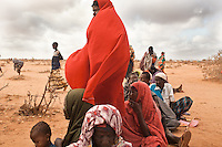 Somali refugees wait in line at the reception center in Ifo camp. Refugees must first go to reception centers for health screening, immunization and finger printing. They will be given an appointment to be registered as refugees.