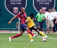 Juan Agudelo (9) of the USMNT clears the ball away from Demar Phillips (12) of Jamaica at RFK Stadium in Washington, DC.  The USMNT defeated Jamaica, 2-0.