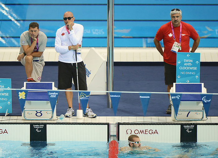LONDON, ENGLAND – 08/24/2012: Coaches Craig McCord, Shane Esau and Reg Shaw watch over the Canadian Swim Team during a training session at the London 2012 Paralympic Games at The Aquatic Centre. (Photo by Matthew Murnaghan/Canadian Paralympic Committee)