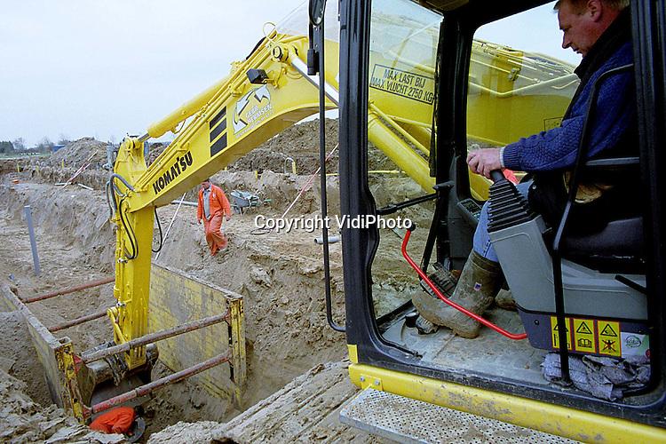 Foto: VidiPhoto..OOSTERHOUT - In het Nijmeegse deel van Oosterhout is begonnen met een nieuwe fase in de Waalsprong. Helemaal zonder problemen gaat het bouwrijpmaken niet. Door de hoge waterstand in de Waal kost het draineren extra moeite. Het grondwater moet nu tot 6 meter diep bemaald worden.