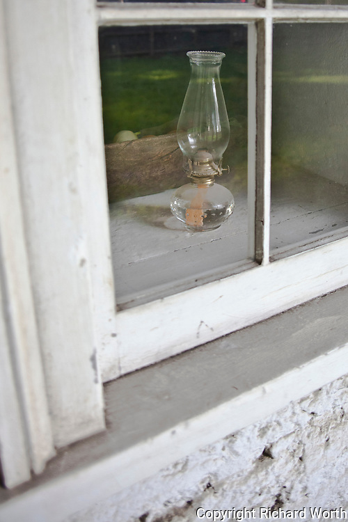 Seen from outside, an oil lamp sits in a window at the Sanchez Adobe Historical Site.