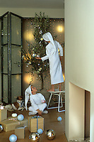 Two boys decorate an olive tree with Christmas decorations in a room scattered with presents and baubles